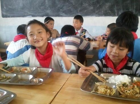排队打饭后,在热腾腾的饭菜面前,孩子们脸上露出了纯真的笑容